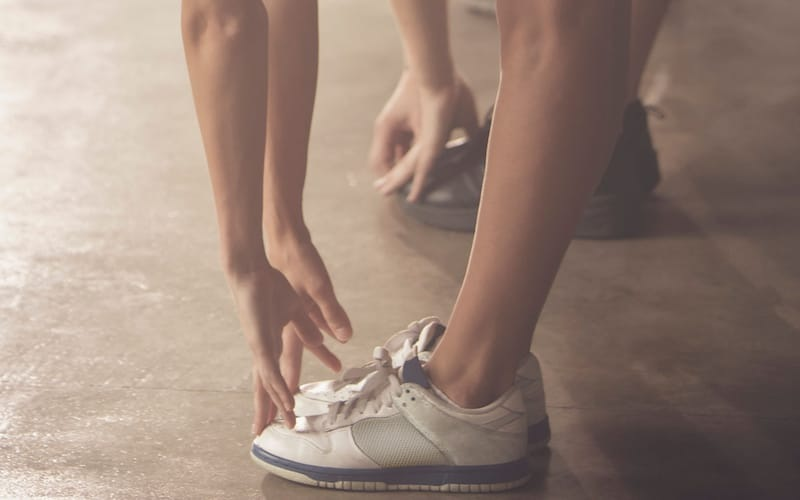 lifestyle image of a woman stretching to touch her shoes